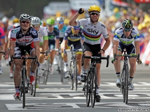 Sky Procycling rider Cavendish of Britain holds up his arm ahead Lotto-Belissol team rider Greipel and Orica GreenEdge rider Goss of Australia as he wins the second stage of the 99th Tour de France cycling race between Vise and Tournai